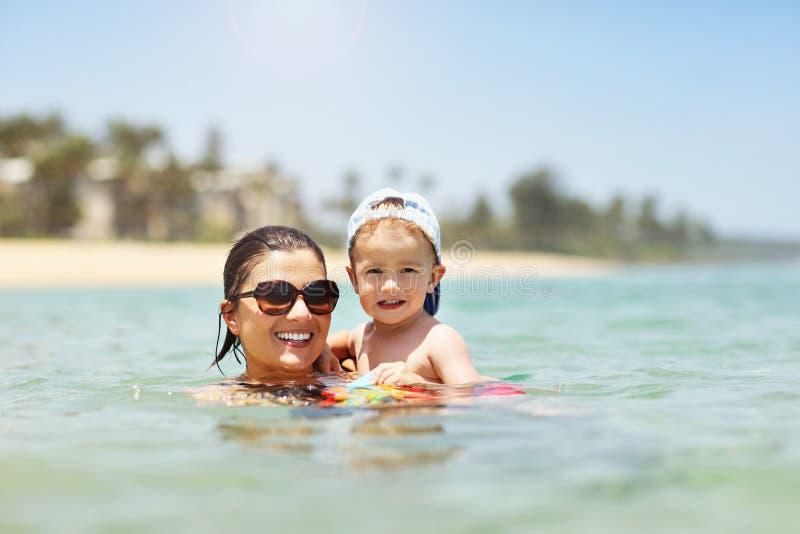 照顾获得在海滩的乐趣与她的小儿子 库存图片