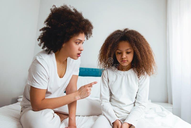 照顾责骂她的女儿,坐在卧室 免版税库存照片