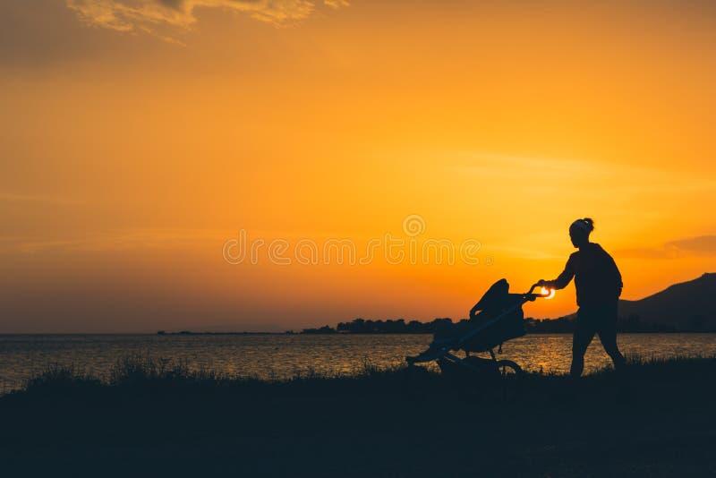 照顾走在与享受母性的婴儿推车的一个海滩. beautifuler, 遗弃情人的.图片