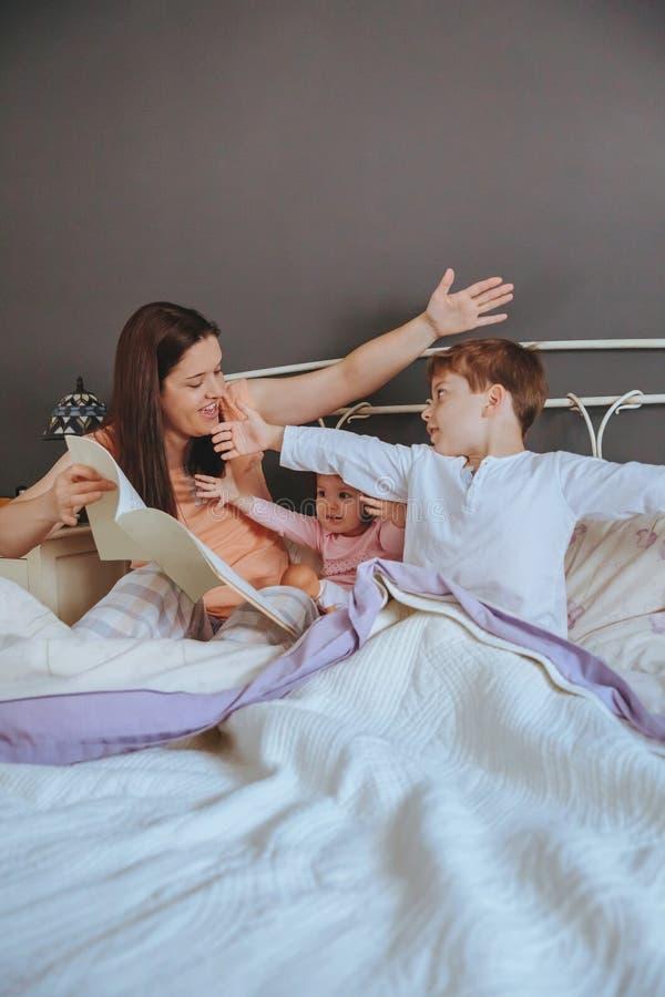照顾阅读书给她的儿子在床上 免版税库存照片