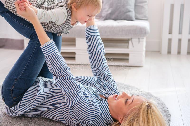 照顾说谎在抱着她逗人喜爱的婴孩的地板上 免版税库存图片
