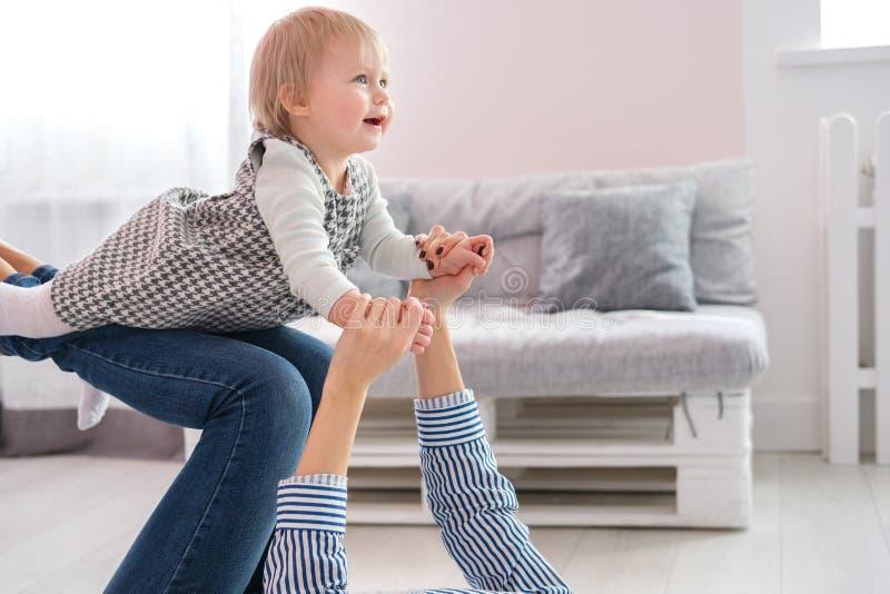 照顾说谎在抱着她逗人喜爱的婴孩的地板上 免版税库存照片