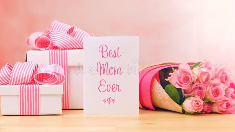 照顾` s天礼物、桃红色玫瑰和最佳的妈妈贺卡在桌上 免版税库存图片