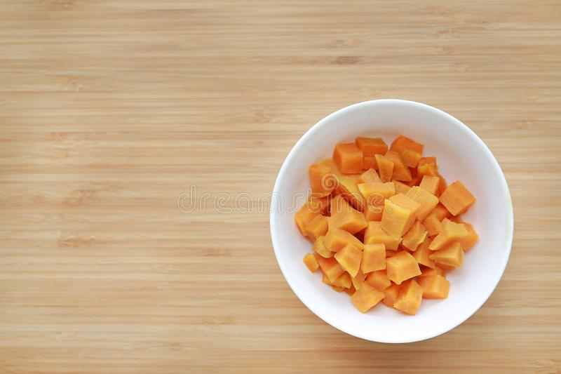 煮沸在白色碗的切好的地瓜反对与拷贝空间的木板背景 免版税图库摄影