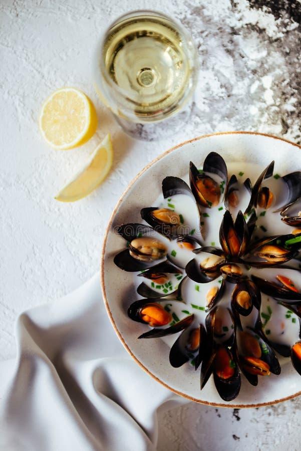 煮沸的淡菜和白葡萄酒在白色石桌上 库存图片