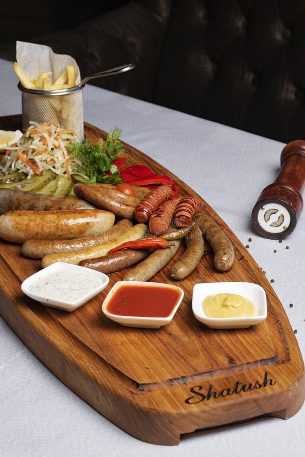煮沸的香肠、乳酪用油煎的蕃茄,荷兰芹和樱桃在餐馆 库存照片