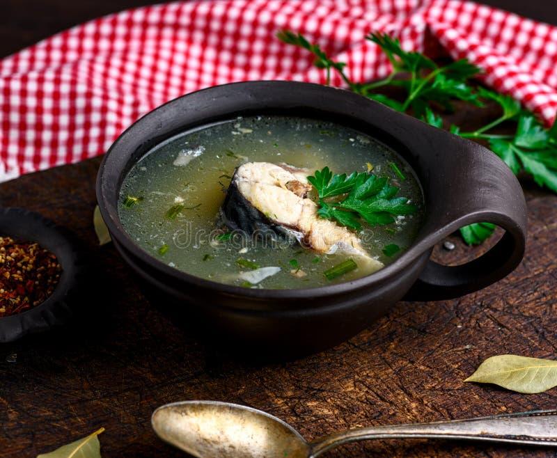 煮沸的鱼汤用在一块棕色黏土板材的鲭鱼 免版税库存照片