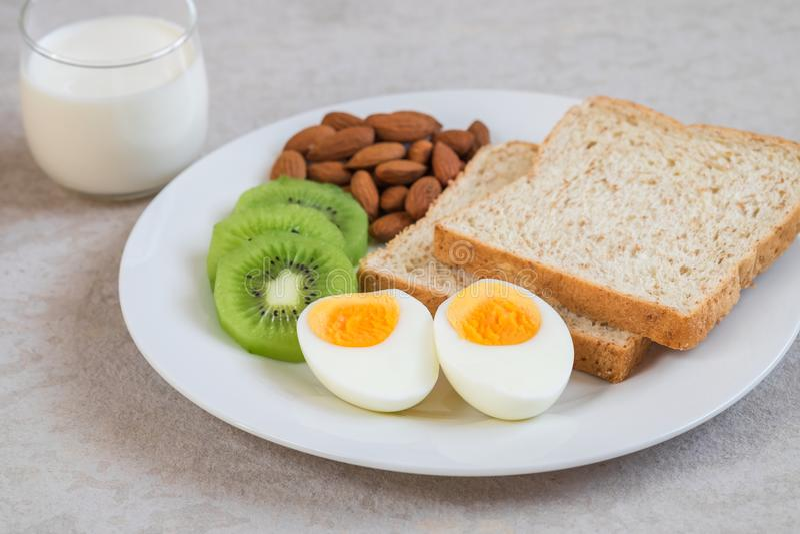 煮沸的鸡蛋、全麦面包、猕猴桃、杏仁和牛奶,健康食物 库存图片