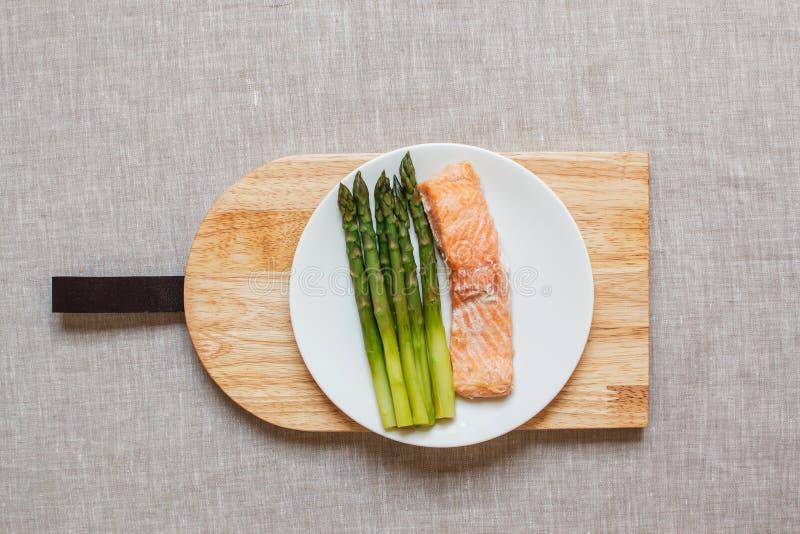 煮熟的三文鱼鱼片用芦笋,健康食品概念,顶视图 免版税图库摄影