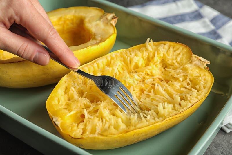 煮熟的意大利粉南瓜妇女刮的骨肉与叉子的在桌上 免版税库存图片