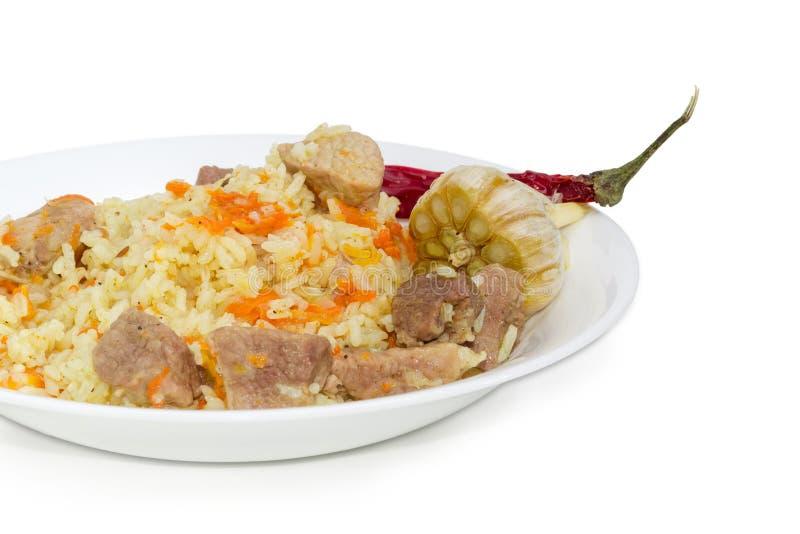 煮熟的肉饭、大蒜和辣椒在白色盘特写镜头 免版税库存照片