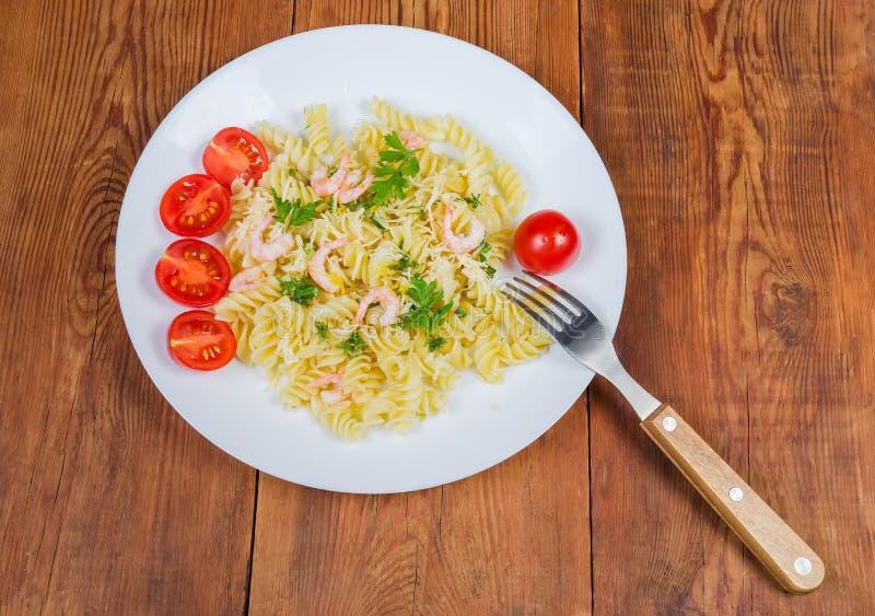 煮熟的螺旋面团用虾、乳酪、西红柿和叉子 免版税库存图片