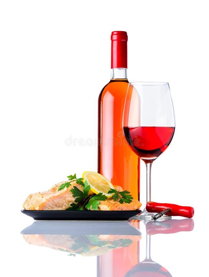 煮熟的鱼用瓶和玻璃在白色背景的玫瑰酒红色 免版税库存图片