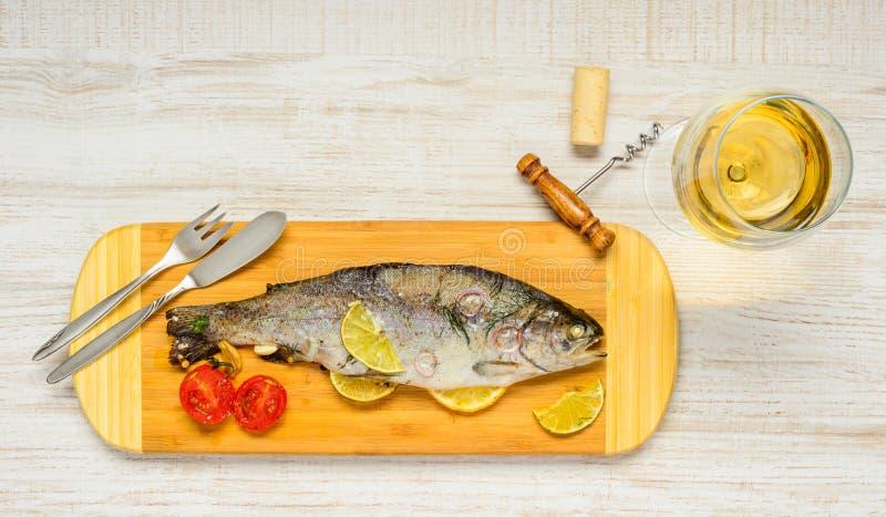 煮熟的鳟鱼鱼用玻璃白葡萄酒 免版税图库摄影