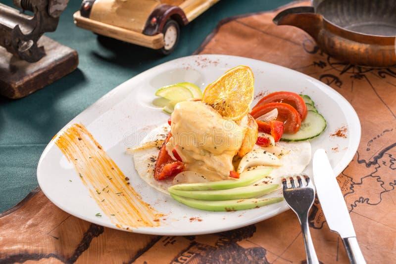 煮熟的鸡胸脯用乳酪调味料用鲕梨和新鲜蔬菜在白色板材在老地图背景 免版税库存图片