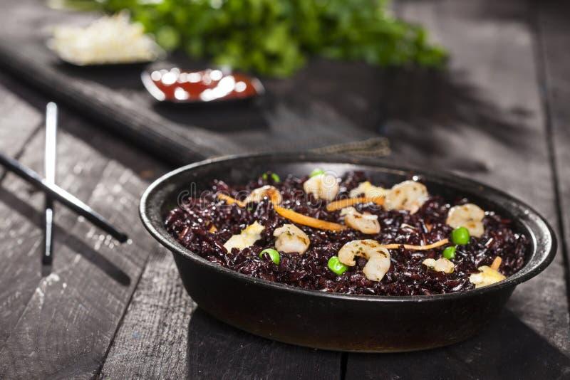 煮熟的黑米用虾和菜在一个盘在木背景 库存照片