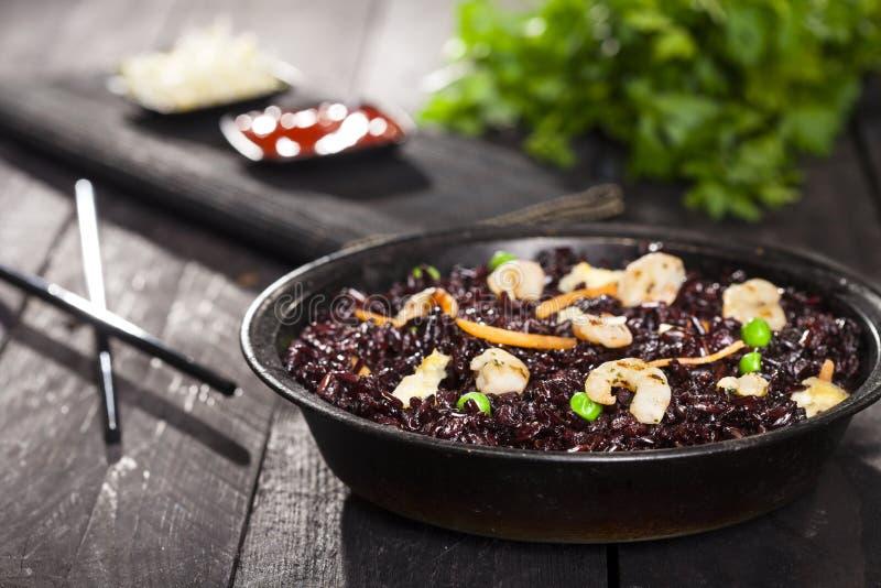 煮熟的黑米用虾和菜在一个盘在木背景 免版税库存图片