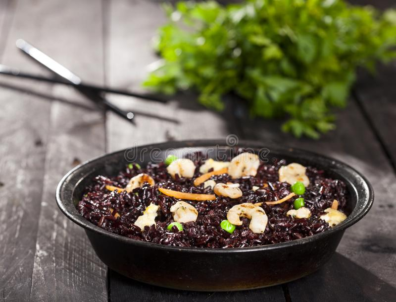 煮熟的黑米用虾和菜在一个盘在木背景 库存图片