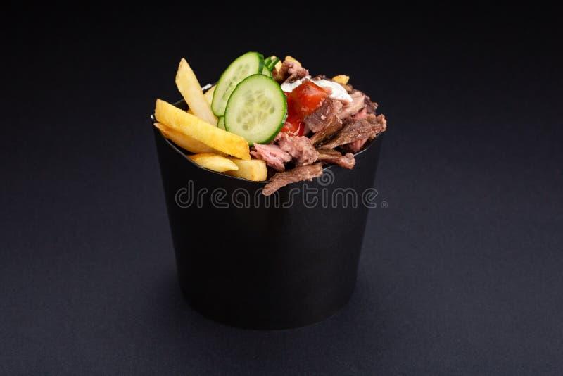 煮熟的shawarma板材用牛肉、薯条、菜和调味汁特写镜头在黑背景 水平的顶视图 库存照片