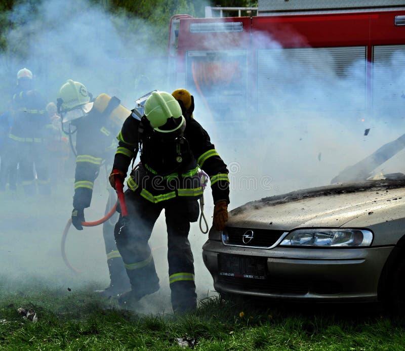 熄灭一辆灼烧的汽车的消防队员 免版税库存图片
