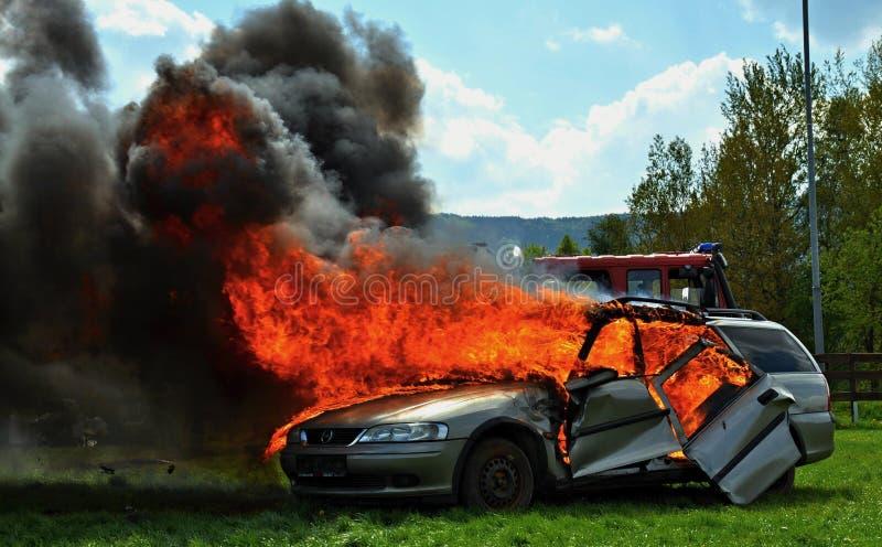 熄灭一辆灼烧的汽车的消防队员 免版税图库摄影