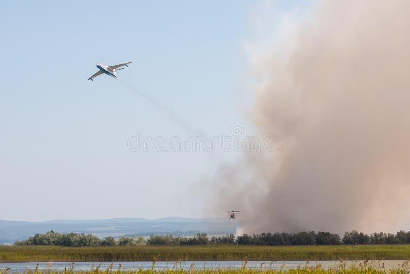 熄灭从空气的火使用一架飞机和一架直升机,有芦苇燃烧的在Anapka Riv的洪泛区 免版税库存图片
