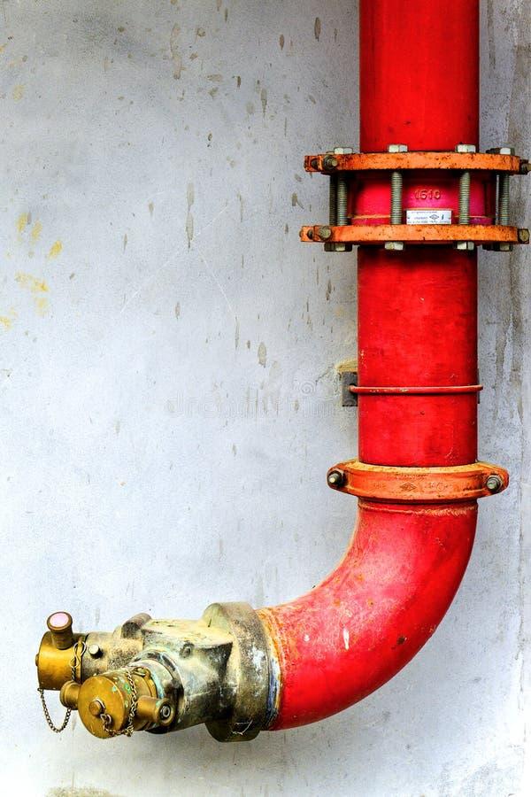 熄灭在混凝土墙上的红色金属管子水 紧急火阀门或Y形状在大厦的水管管 安全设备a 库存照片