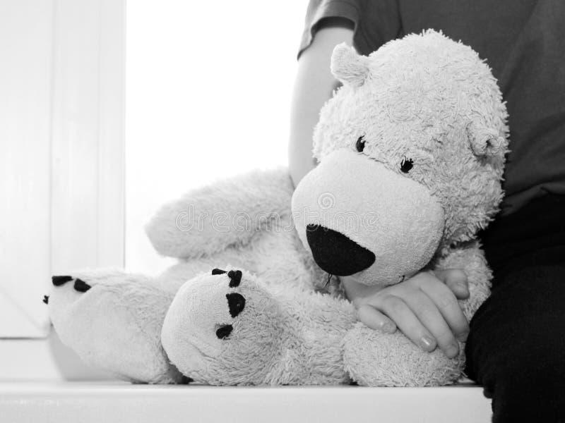 熊哀伤的玩具坐窗口 库存照片