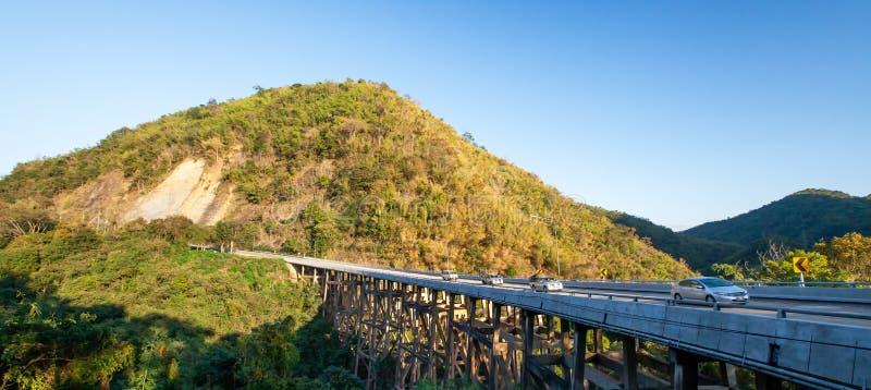 熊山桥梁的风景在黄昏的,金黄日落在驾车发光横跨桥梁和山脉 免版税库存图片