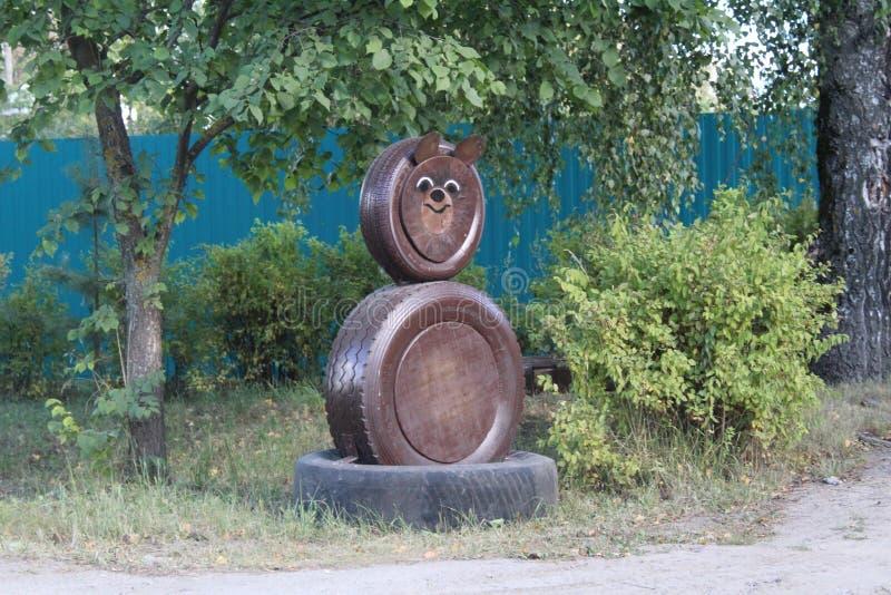 熊的图露天做用他的手由汽车的轮子 库存图片