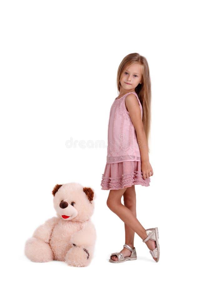 熊逗人喜爱的女孩女用连杉衬裤 摆在与玩具的时兴的孩子隔绝在白色背景 儿童无罪概念 库存照片