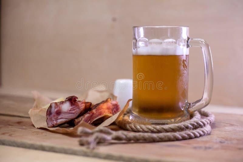 熏制的排骨片断与一杯的啤酒 免版税库存照片