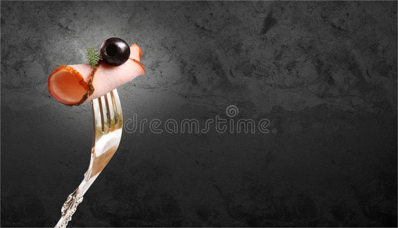 熏制的肉开胃片断用橄榄和在叉子别住的莳萝小树枝对一个黑石墙 免版税图库摄影