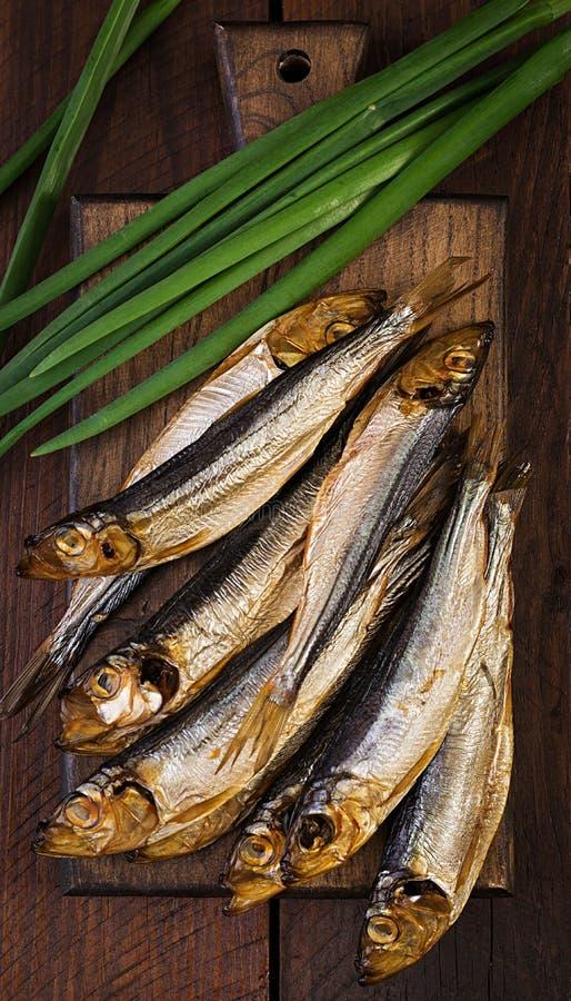 熏制的西鲱和大葱在一个切板 免版税图库摄影