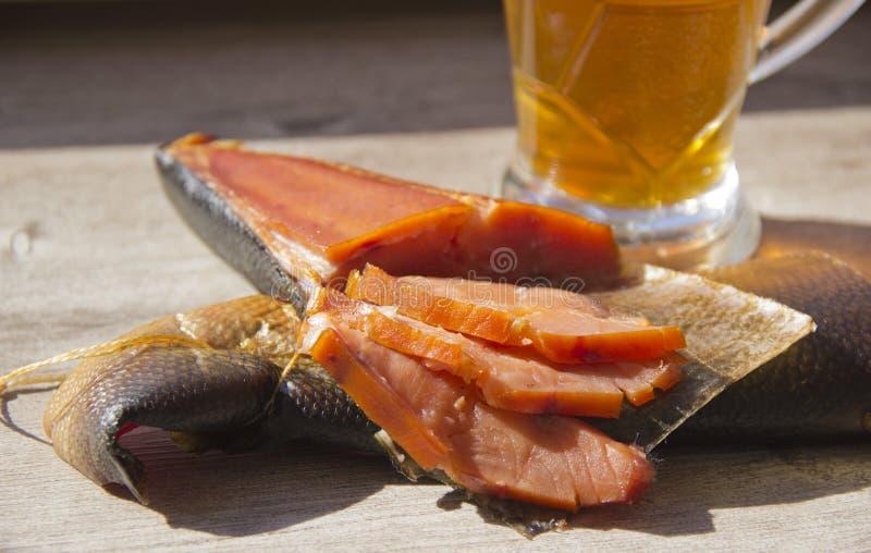 熏制的鱼和一杯在木背景的啤酒 免版税库存图片
