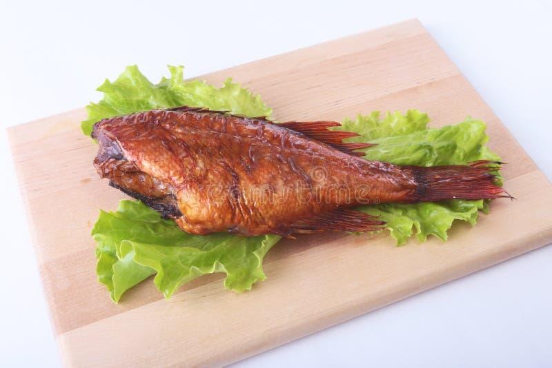 熏制的鱼和柠檬在绿色莴苣叶子在白色背景隔绝的木切板 库存图片