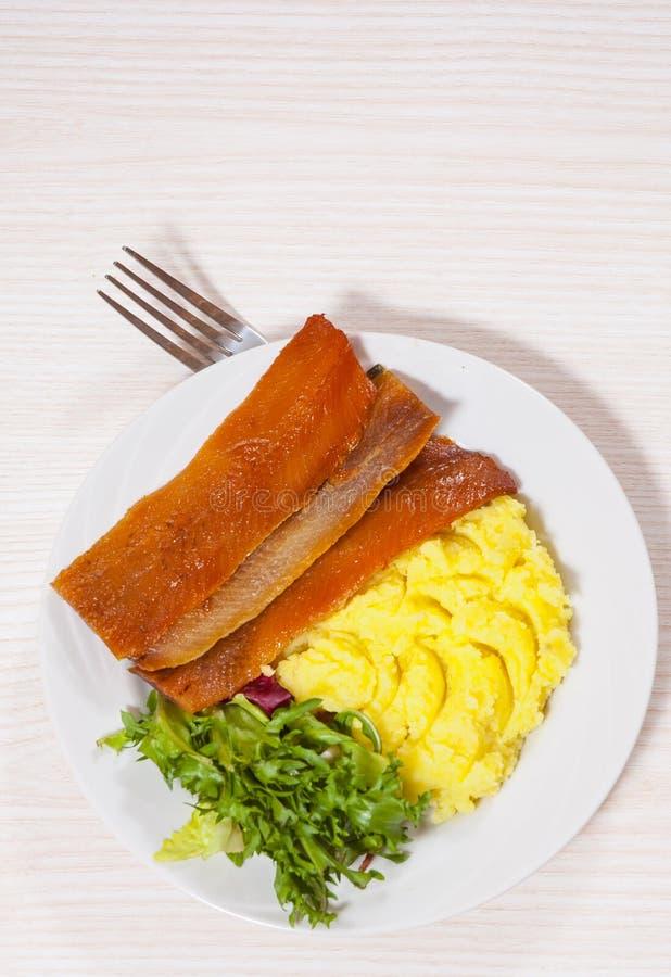 熏制的鱼片用土豆泥和沙拉 免版税库存照片