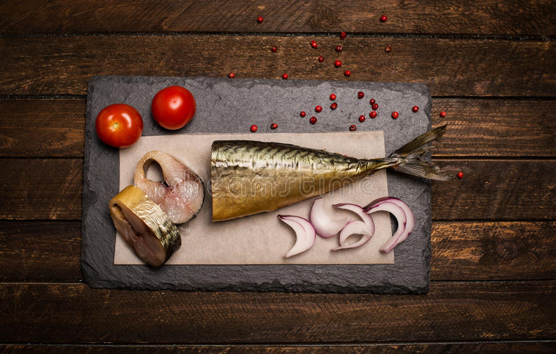 熏制的鲭鱼背景 在板岩板,上面的熏制的鲭鱼 库存照片