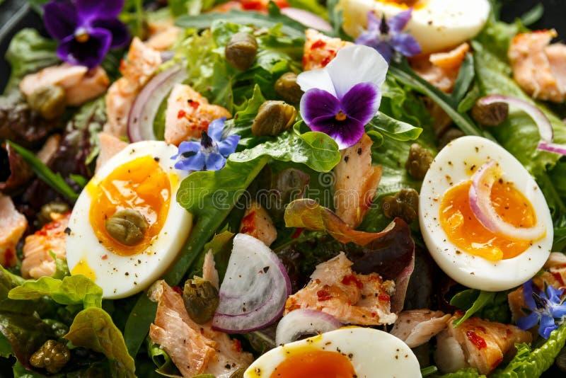 熏制鲑鱼和粘上果酱的半熟自由放养的鸡蛋和雀跃沙拉与可食的琉璃苣和蝴蝶花花 免版税库存图片