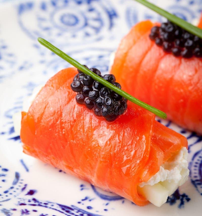 熏制鲑鱼滚动用乳脂干酪,黑鱼子酱 免版税图库摄影