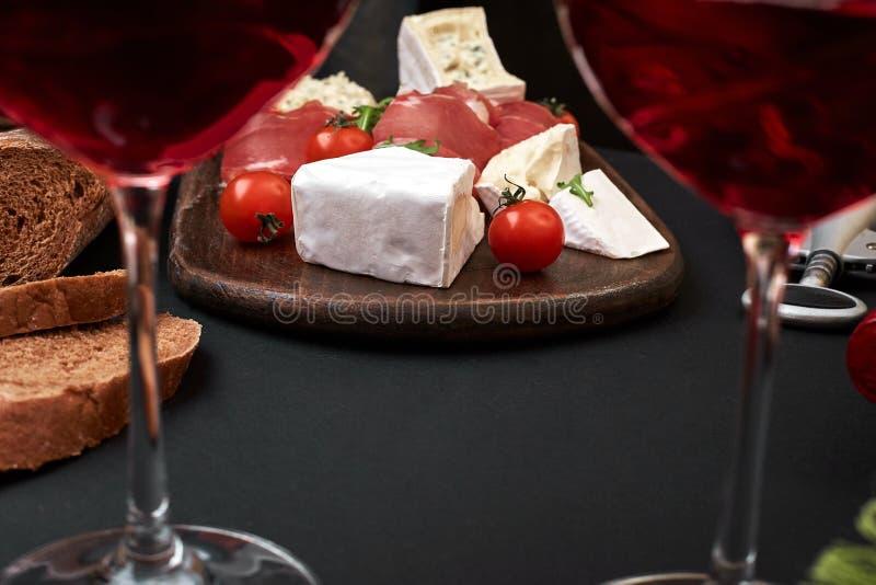 熏火腿、蒜味咸腊肠、长方形宝石切片、蕃茄和nutson土气木板,两杯在黑色的红葡萄酒 免版税库存照片