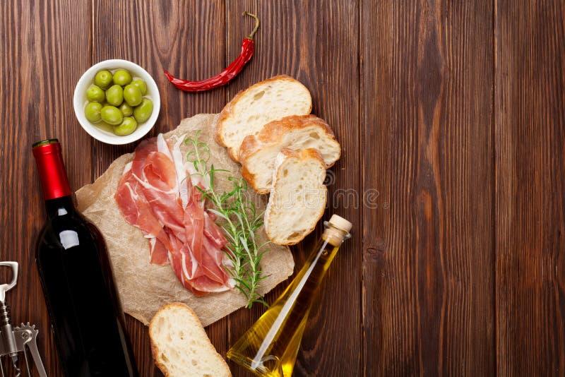 熏火腿、酒、橄榄、巴马干酪和橄榄油 免版税图库摄影