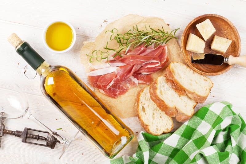 熏火腿、酒、橄榄、巴马干酪和橄榄油 库存照片