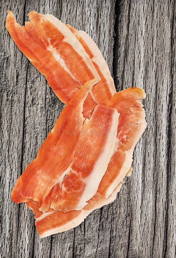 熏火腿抽了猪肉非常老木表面上的火腿切片 免版税库存照片