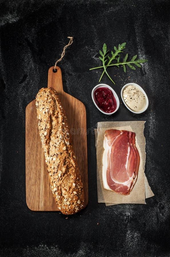 熏火腿(帕尔马火腿)三明治食谱-在黑色的成份 库存照片