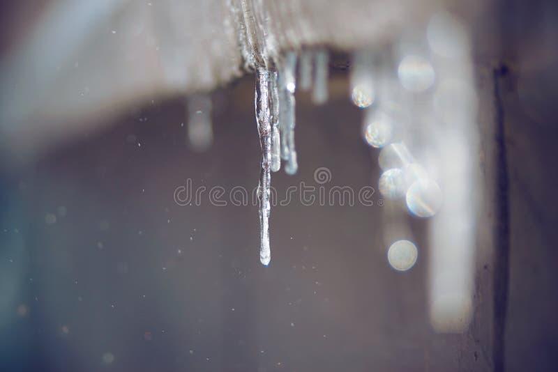 熔化的冰柱从老屋顶垂悬 免版税库存图片