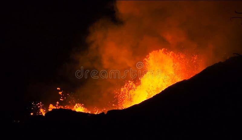 熔岩的夜爆发从火山的 红色从火山的嘴飞溅 免版税图库摄影