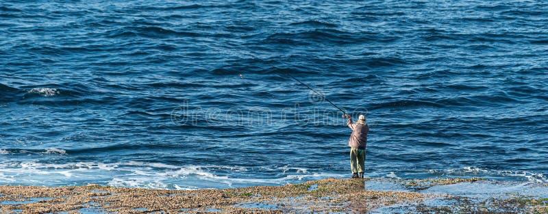 熔铸他的石楠诡计岩石钓鱼的渔夫 免版税库存图片