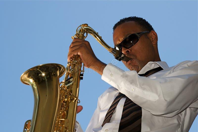 熟悉内情的萨克斯管吹奏者年轻人 免版税库存图片