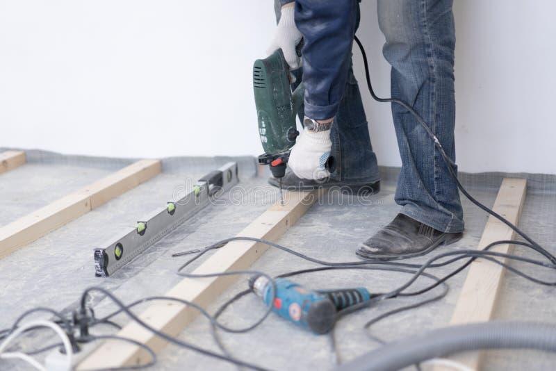 熟练木匠登上松木地板-环境友好的地板 对混凝土的拧紧的滞后 库存照片